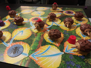 A game board covered in spaces that look like fallen elm leaves, with several plastic echidna figurines distributed around the board. Some of these have coloured bugs mounted on them.