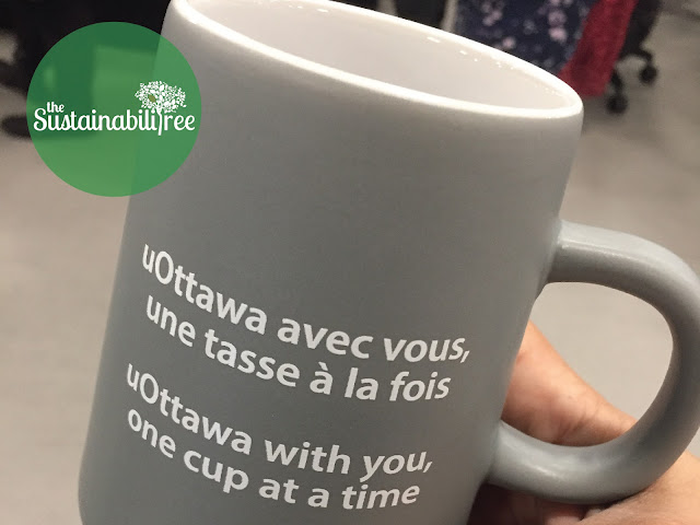 A reusable uOttawa coffee mug with a slogan on it