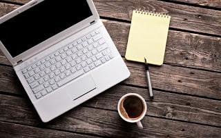 ordenador, bloc de notas y café