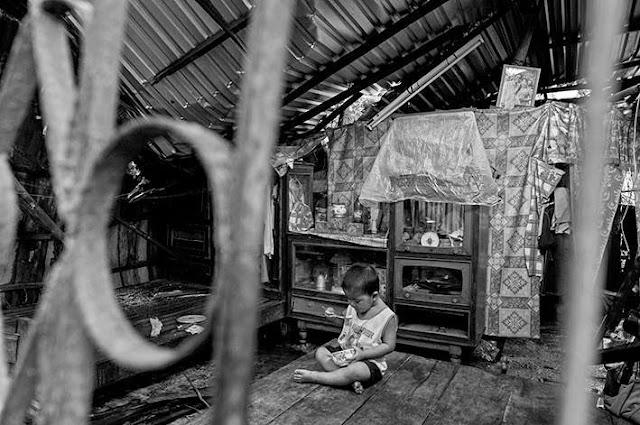 Mọi người tất bật với công việc khắc phục hậu quả nên bé ăn sáng một mình trong căn nhà oằn mái.