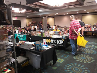 A small section of the hotel convention area with several tables, each set up with a variety of games or other products for sale. Some people can be seen either working the booth or browsing the wares.
