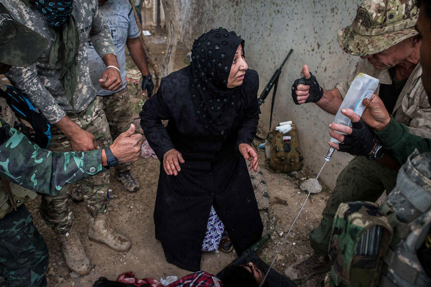 Powerful Heart-Breaking Pictures Of The Battle Of Mosul - A woman learns from American and Burmese medics that her son will survive a bullet wound in the leg
