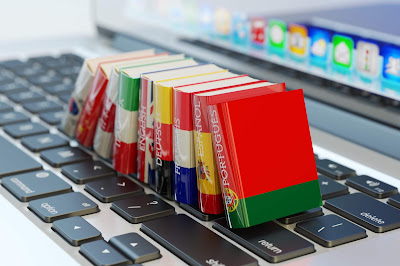 photo of mini language books on laptop keyboard and screen in background