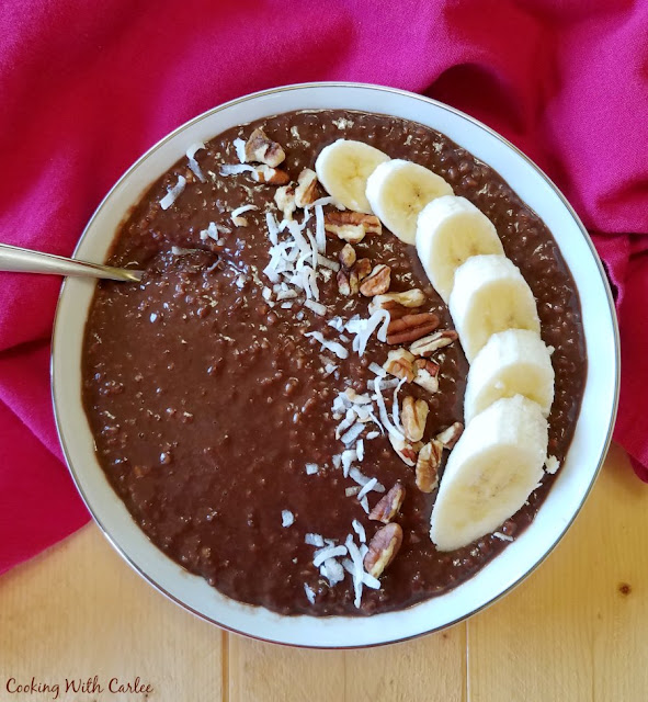 bowl of chocolate steel cut oatmeal topped with banana, pecans and coconut