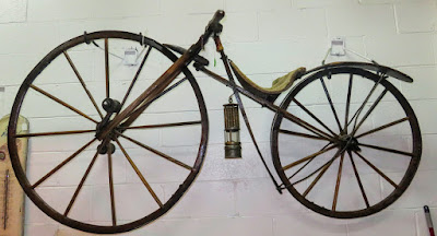 1800s bicycle hanging on wall