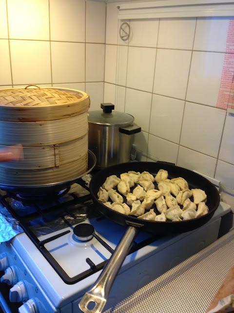 Koekenpan en stoommandje met dumplings op het gasfornuis