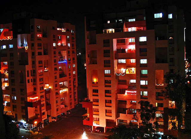two apartment buildings lighted up for Diwali