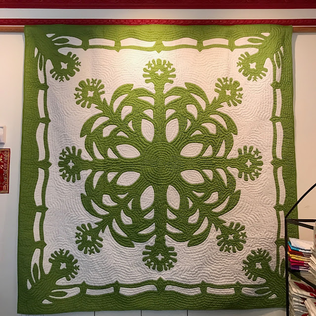 Hawaiian quilt with a green and white design