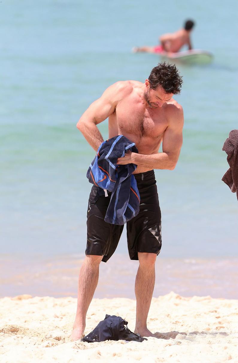 Hugh Jackman Displays Bulging Biceps As He Runs Out Of The Sea Topless