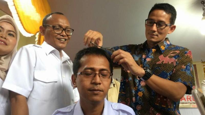 Sandiaga Uno menggunting rambut pendukungnya