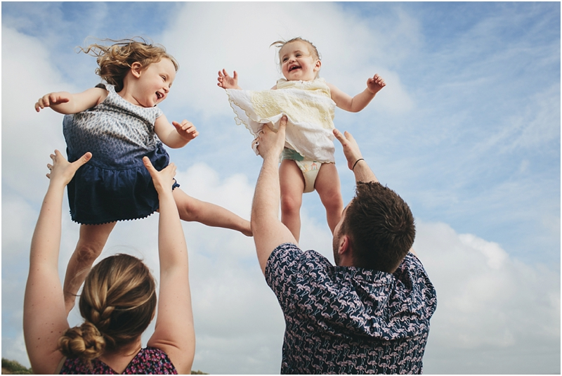 Two children laughing as their parents throw them in the air