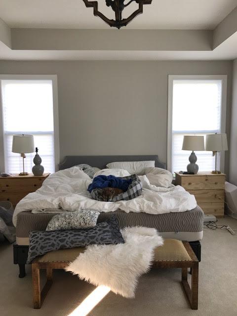 Bedroom with bed between two windows