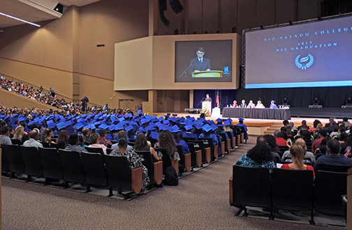 photo of 2017 graduation ceremony.  wide shot of stage and students in caps and gowns.