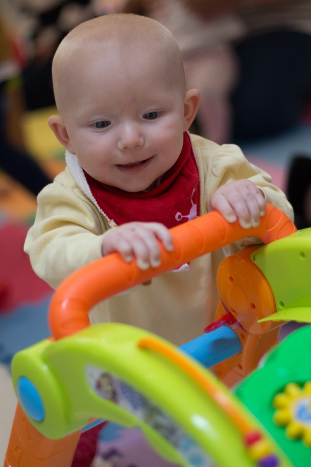 A baby standing up and holding on to a brightly coloured plastic walker