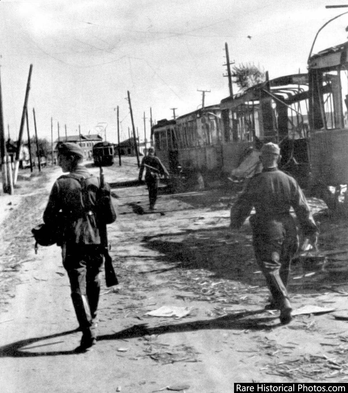 Germans walk past burnt tram cars on the streets of Stalingrad.