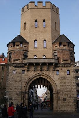 Braunes, burgartiges Gebäude mit Falltor, einem großen Turm in der Mitte und zwei kleineren Halbtürmen