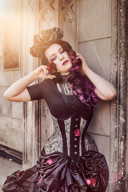Women's steampunk gothic clothing with a floral crown, black skirt, corset, and top.