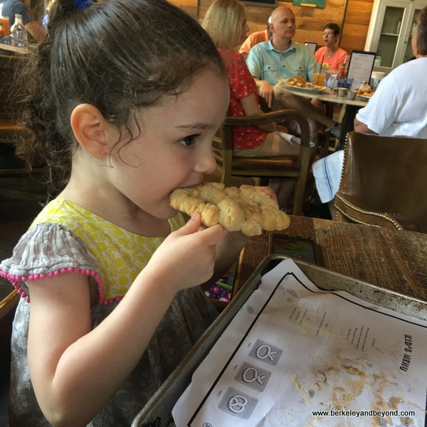 little girl eats baked pretzel she made at Southerleigh Fine Food and Brewery in San Antoniio, Texas