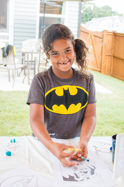 Girl coloring a batman printable at a batman party
