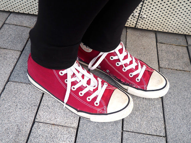 On The Move | outfit details of red high top Converse sneakers