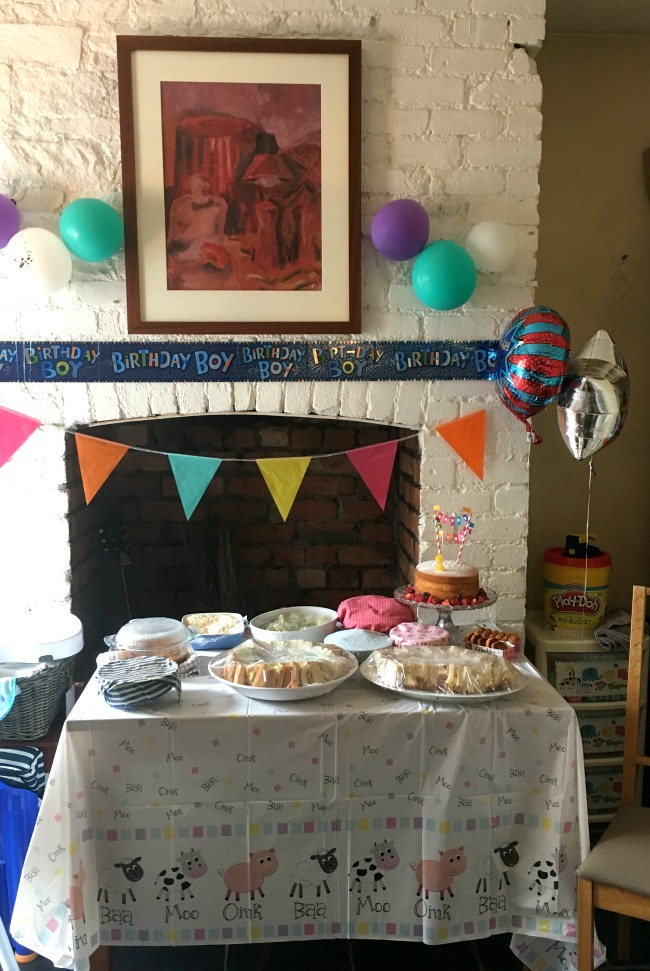 Bees-first-birthday-food-on-table-with-banners-and-balloons