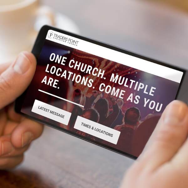 Man holding smartphone views the Traders Point Christian Church website redesign