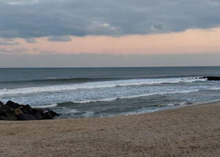 Breaking waves at the beach under gray clouds as the late afternoon sky turns pink, Asbury Park, New Jersey