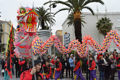Pic of dancers holding dragon above their heads with sticks in carnival