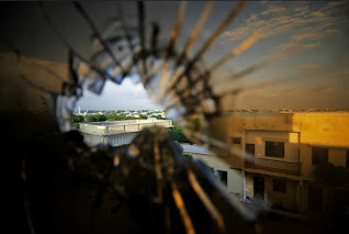 Skyline beyond the northern suburbs of Mogadishu is seen through a bullet hole