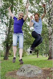Kirsi Käyhty ja Meri-Sisko hyppäävät iloisina kiven päältä ilmaan.