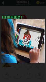 ребенок рисует на планшете за столом