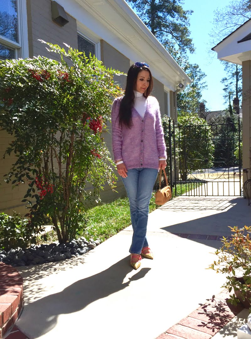 Wearing long lavender mohair cardigan with a white turtleneck under and jeans. Gold glitter mary janes and holding a small baguette camel purse.