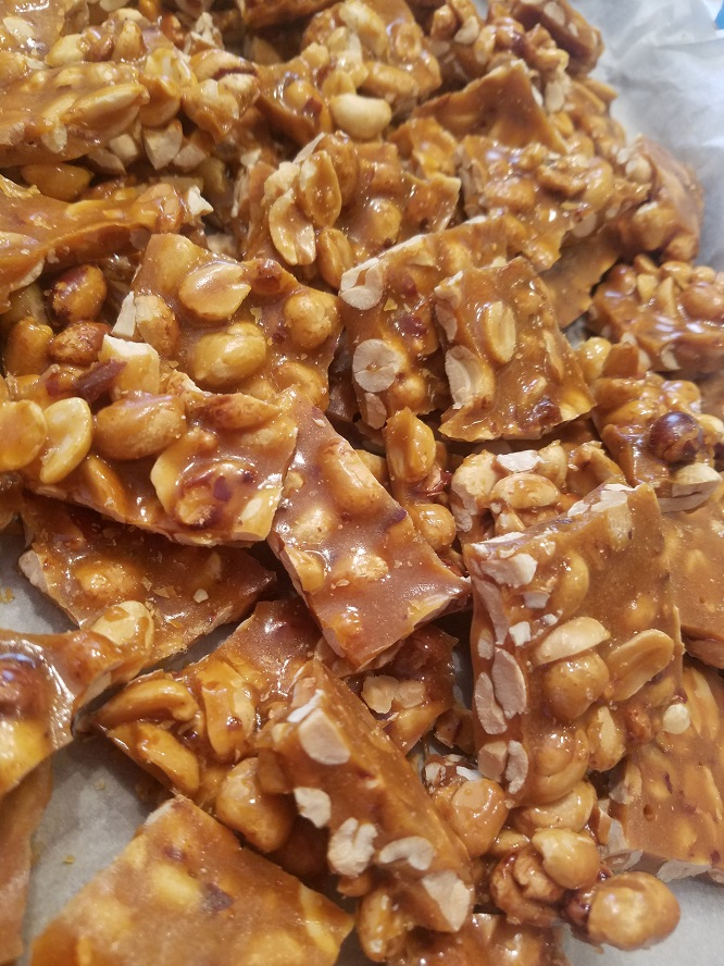 buttery homemade peanut brittle and old recipe and easy to make this is on parchment paper so it won't stick
