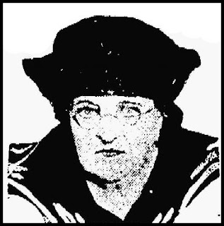 A headshot of a plump white woman just past middle age, with piercing eyes, a sharp nose, and tiny pursed lips. She wears a dark hat, sailor collar, and wire-rimmed glasses