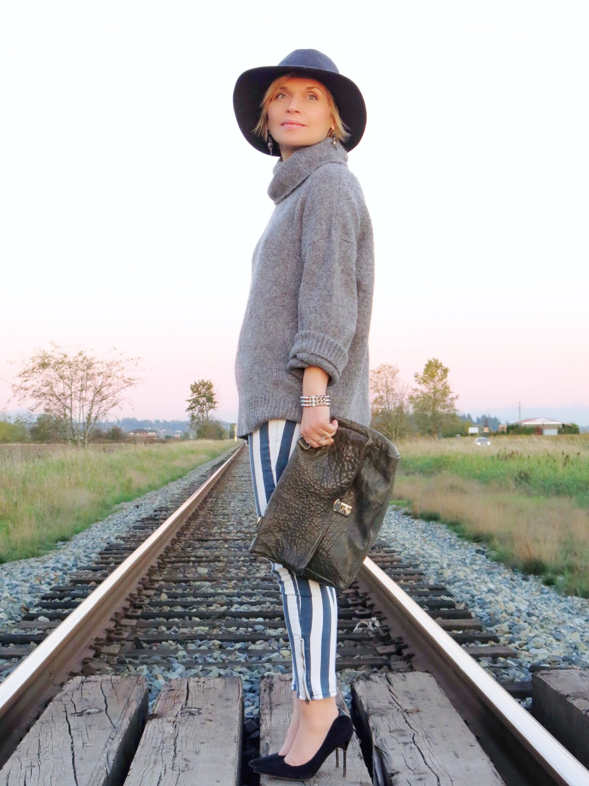 styling an oversized turtleneck sweater with striped jeans, pumps, and a floppy hat