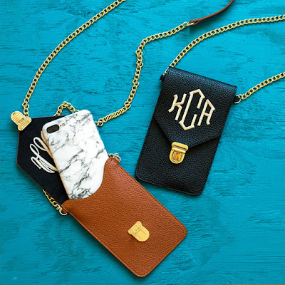 monogrammed brown and black phone crossbody bags on blue background