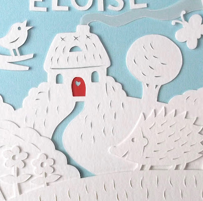 cut paper picture of hedgehog and cottage