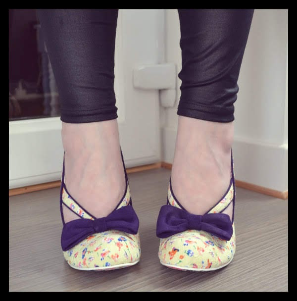 feet facing forward wearing cream floral shoes with purple bow