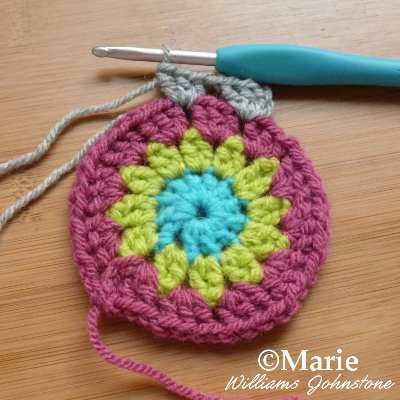 Double crocheting in gray yarn around a circle