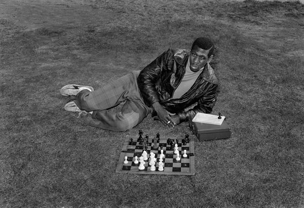 retrato de un hombre afroamericano jugando ajedrez sobre el pasto de un parque