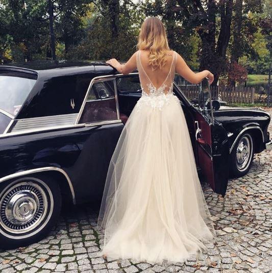 Zjawiskowa suknie ślubna z dekoltem na plecach przy zabytkowym samochodzie.