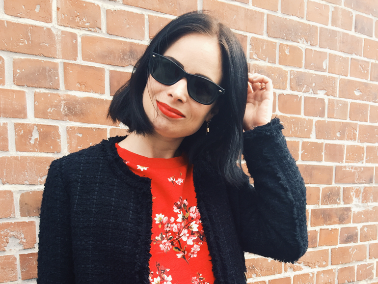 ROUGE & NOIR   June Gold wearing a black Zara coat and a red cherry blossom print h&m sweater