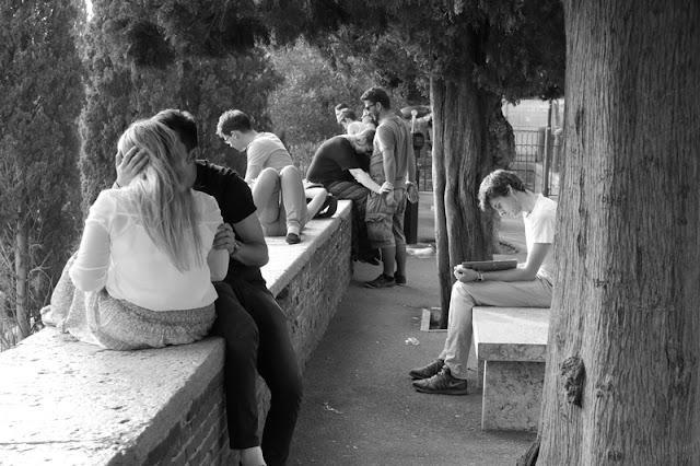 Street photography a Verona. Ragazzo che studia in mezzo ad innamorati
