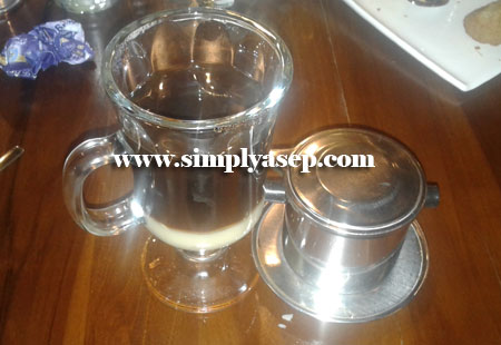 UTUH : Vietnam drip coffee saat belum diaduk keadaannya seperti ini.  Susu ada di bagian bawahnya. Saringan kopi ada di sebelah kanan.  Foto Asep Haryono