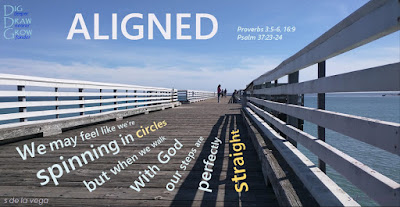 "Pier boardwalk bearing the words ""aligned: We may feel like we're spinning in circles, but when we walk with God, our steps are perfectly straight"