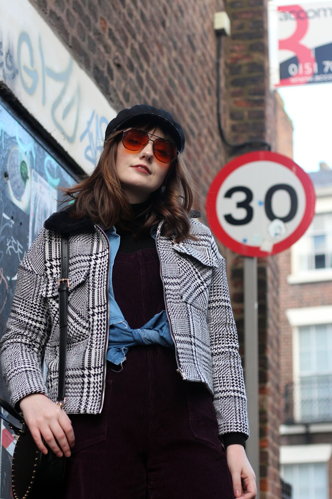 70s style fashion blogger, black baker boy cap, orange aviators, monochrome check jacket from pretty little thing, purple cord dungarees