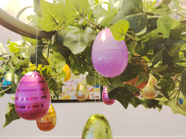Take your Easter Egg hunt inside with this fun Easter decoration. It's so easy to decorate your dinning room chandelier with beautiful Easter eggs and greenery to make a stunning Easter Egg Chandelier that will bring some extra sparkle and shine to your Easter dinner.