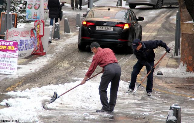Coreanos limpiando nieve de la calle en Seúl