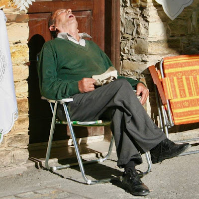 Man sitting in a lawn chair, sleeping with his head back and face pointing up with mouth open.