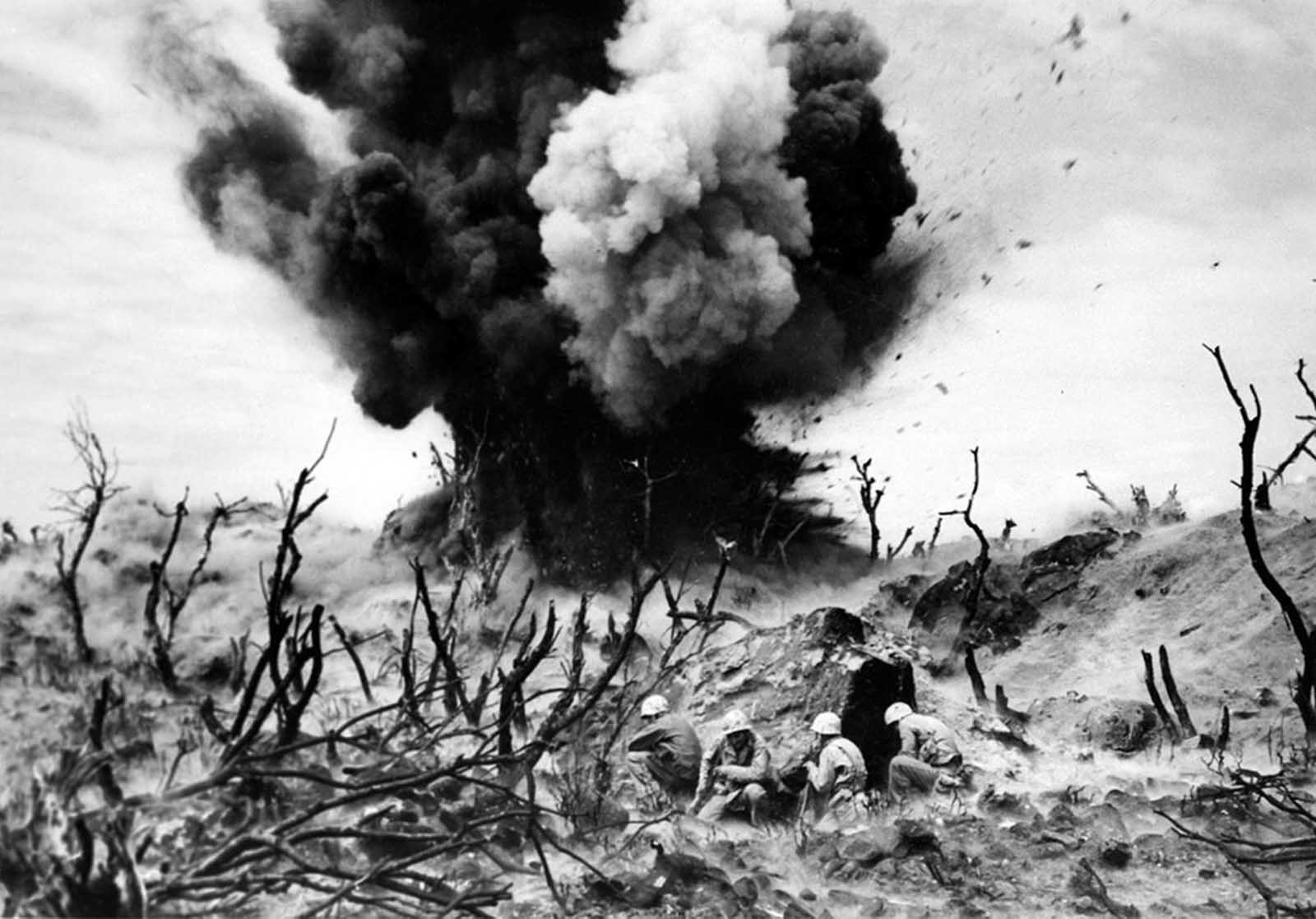 An attack on one of the caves connected to a three-tier blockhouse destroys the structure on the edge of Turkey Nob, giving a clear view of the beachhead toward the southwest on Iwo Jima, as U.S. Marines storm the island on April 2, 1945.